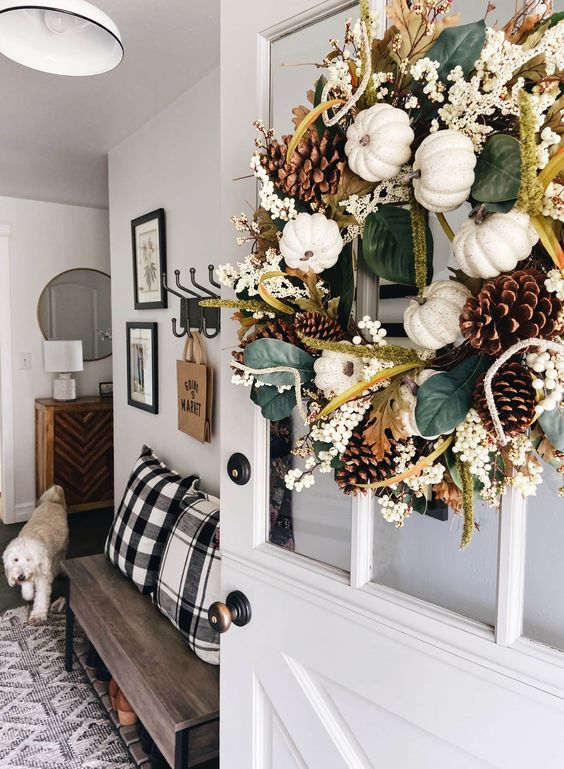 a lovely fall or Thanksgiving wreath with leaves, berries, white pumpkins and pinecones is a stylish decoration