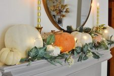 a lovely modern Thanksgiving mantel with greenery, white blooms and large natural pumpkins and candles