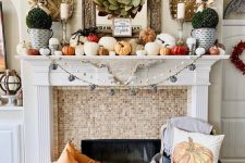 a lovely modern farmhouse Thanksgiving mantel with lots of pumpkins of various sizes, greenery topiaries, a leaf wreath and woden baskets