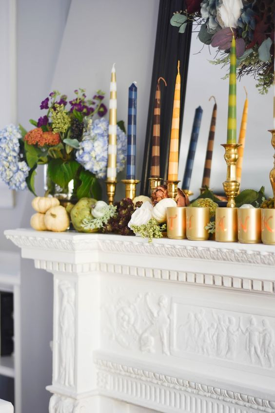 a modern and bright Thanksgiving mantel with real fresh veggies, greenery, bold blooms, bright striped candles and gold candleholders
