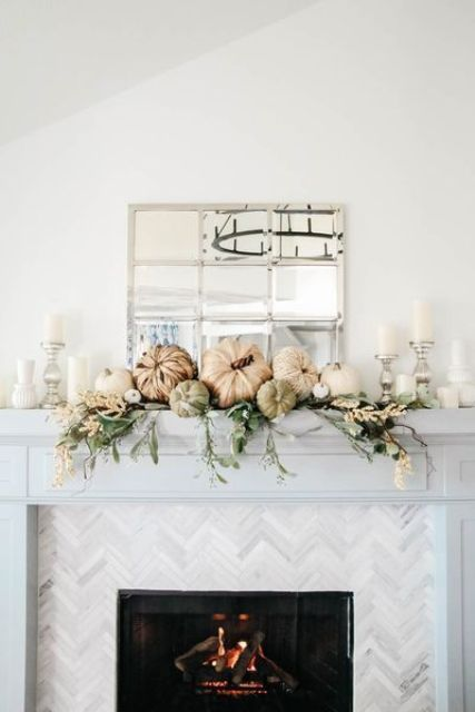 a neutral Thanksgiving mantel with greenery, white blooms, pumpkins and neutral candles is chic and beautiful