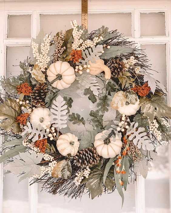 a pretty neutral textural fall or Thanksgiving wreath of pale leaves, white pumpkins, pinecones and twigs is a lovely idea