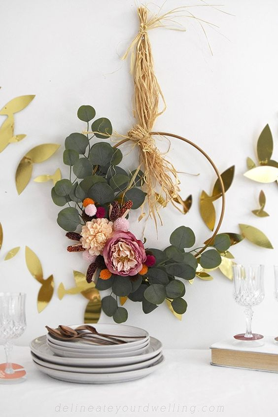 a refined and cute boho Thanksgiving wreath with greenery, pink and blush blooms and some hay is a cool idea to try