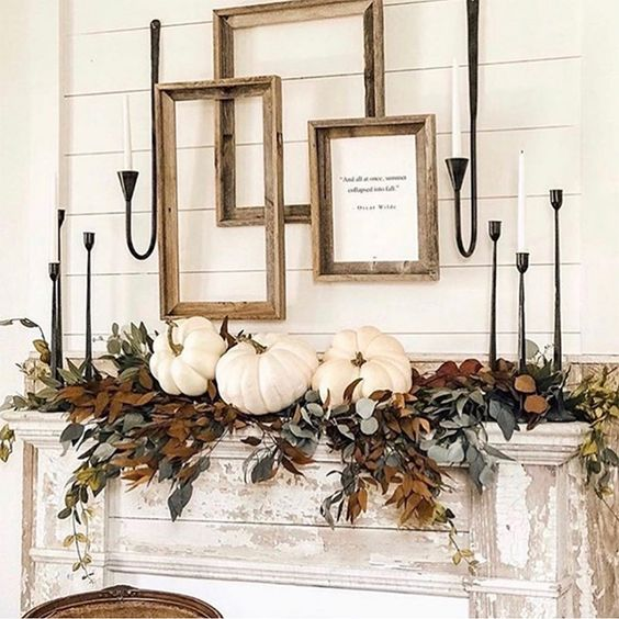 a refined vintage Thanksgiving mantel with lots of greenery and dried leaves, white pumpkins, white candles and empty frames for a farmhouse touch