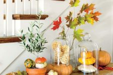 a rustic Thanksgiving console with bright leaves, pumpkins and gourds is a pretty decoration