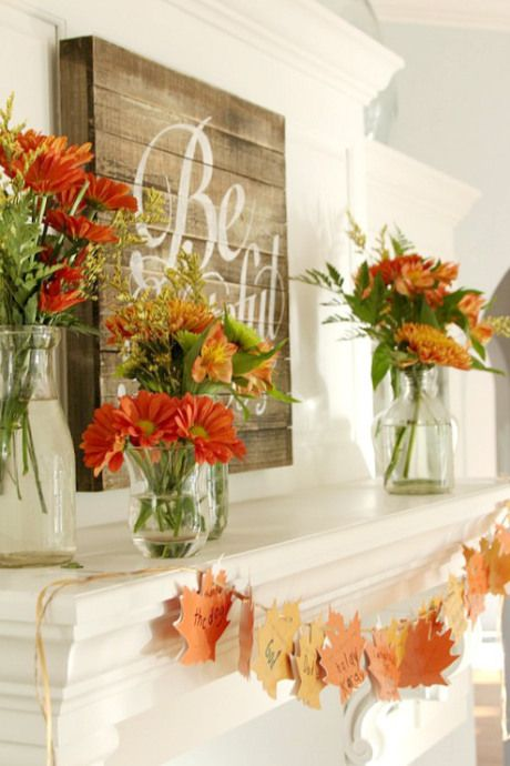 a rustic chic Thanksgiving mantel with bold blooms and greenery arrangements, a wooden sign and paper fall leaf garland