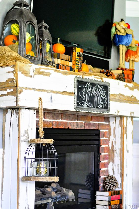 a shabby chic Thanksgiving mantel with lanterns with pumpkins, books, bold velvet pumpkins and pinecones