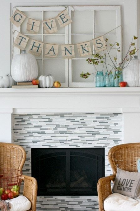 a simple Thanksgiving mantel with oversized white pumpkins, bright apples, branches with leaves and burlap banners