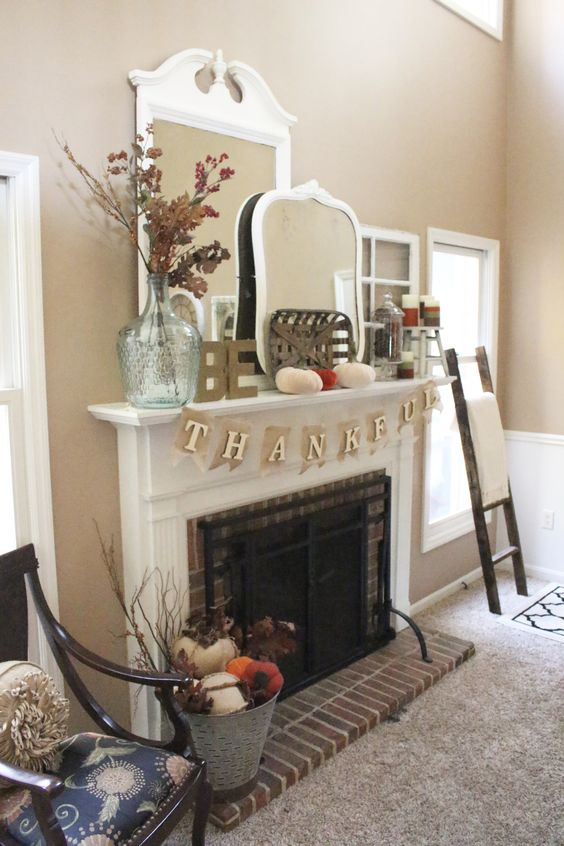 a simple Thanksgiving mantel with velvet pumpkins, oversized vintage mirrors, a dried leaf arrangement in a glass vase plus candles