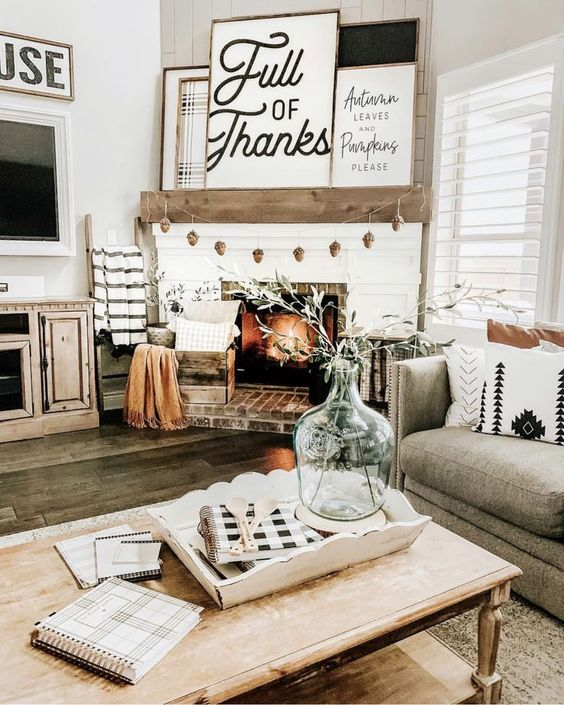 a simple farmhouse Thanksgiving mantel with a pinecone garland, several signs and pillows and a blanket