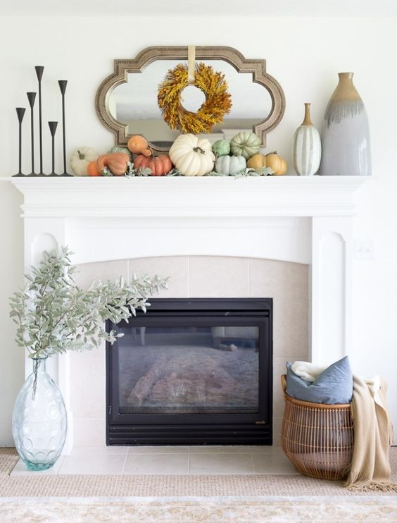 a stylish modern Thanksgiving mantel with a leaf wreath, neutral and pastel pumpkins and large vases