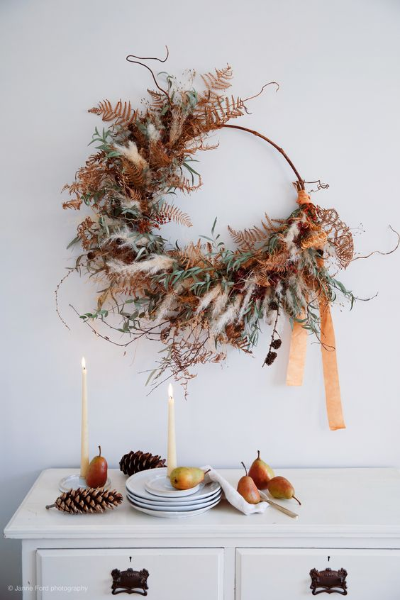 a unique and super textural Thanksgiving or fall wreath of pampas grass, greenery, dried leaves, pinecones and long ribbons is amazing