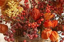 a vase covered with corn cobs, dried blooms, berries and soem twine is a bold centerpiece for fall or Thanksgiving