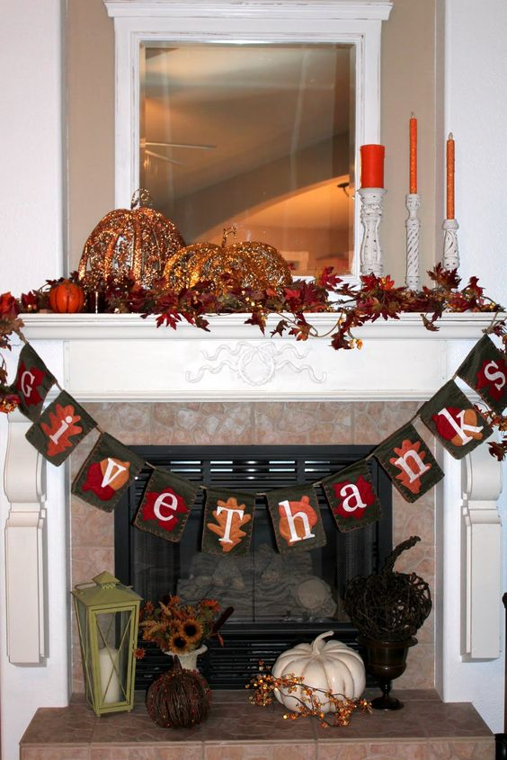 a vintage Thanksgiving mantel with bold leaves, pumpkins of porcelain and lights, a fabric garland and orange candles