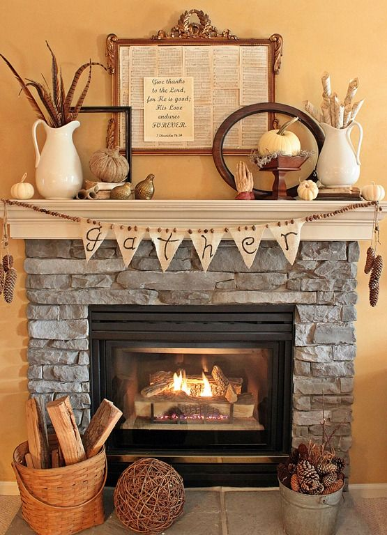 a vintage and rustic Thanksgiving mantel with a wooden bead and burlap garland plus pinecones in a bucket, mini pumpkins, feathers, ,etal gourds and signs