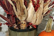 a wooden basket with berries and corn husks plus pumpkins next to it compose a lovely rustic decoration