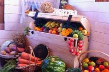 a wooden chest with lots of veggies and fruits and baskets with them around is a pretty rustic decoration to rock