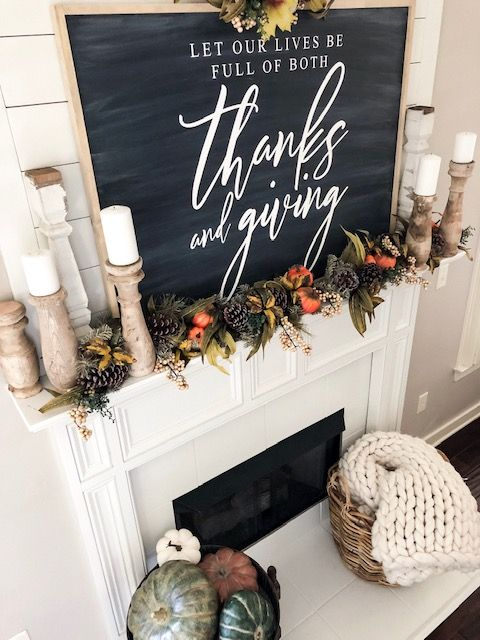 a woodland Thanksgiving mantel with a chalkboard, greenery, pumpkins, pinecones, candles in wooden candleholders