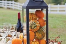 an oversized lantern filled with pumpkins and with berries is a cool rustic decoration you can easily make