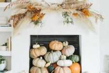 heirloom pumpkins stacked in the fireplace, a dried grass overhead installation and some firewood for fall and Thanksgiving