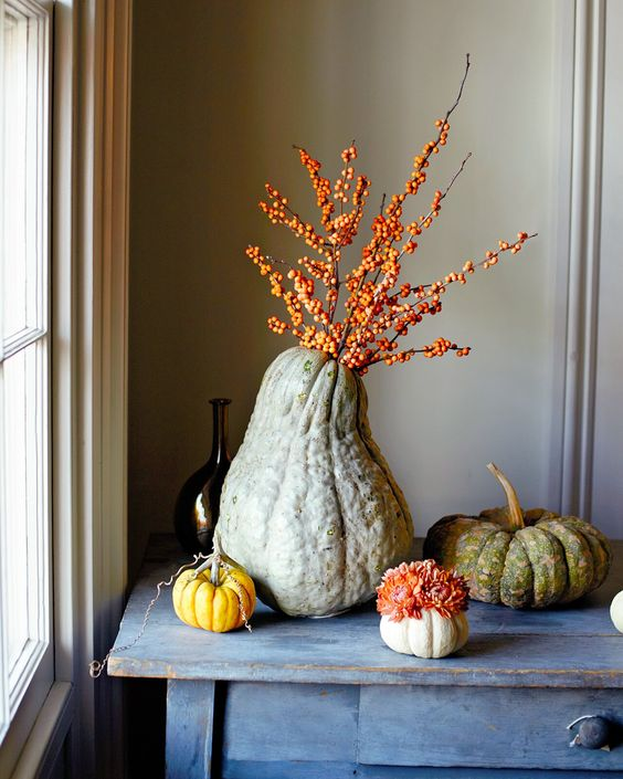heirloom pumpkins with blooms and an oversized gourd with berried branches is a lovely all-natural decoration