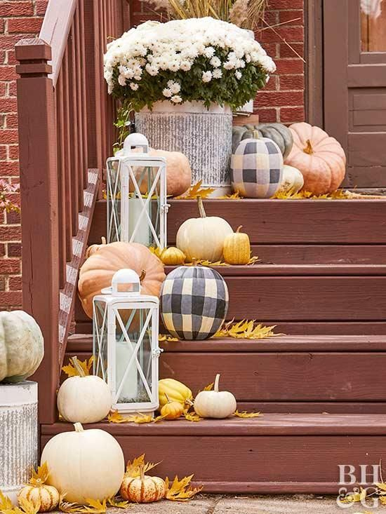 neutral and plaid pumpkins, bright leaves, candle lanterns and white blooms in a pot for decorating outdoors