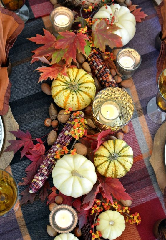 rustic Thanksgiving decor of pumpkins, bold leaves, berries and corn cobs is lovely for fall, too