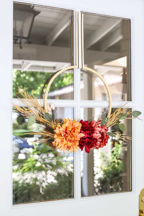 such a cute and bright fall or Thanksgiving wreath with bold blooms, greenery and wheat is a very bold and easy to DIY piece