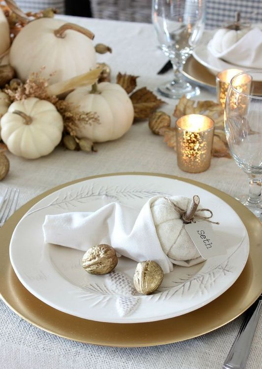 white pumpkins, dried leaves, gilded nuts and candles in mercury glass candleholders for a chic and refined Thanksgiving tablescape