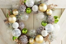 a Christmas wreath made of white and gild ornaments, snowy pinecones and snowy evergreens