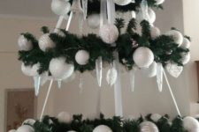 a beautiful Christmas chandelier with white and frosted shiny white Christmas ornaments and ribbons