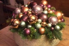 a bowl with a whole arrangement of metallic and pink ornaments and evergreens is a cool holiday centerpiece