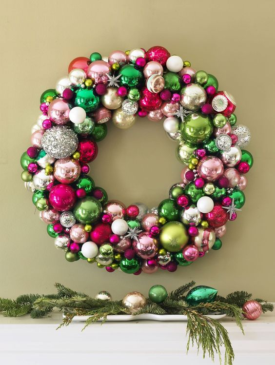 a colorful Christmas wreath of ornaments of green, pink, silver, blush balls and snowflakes