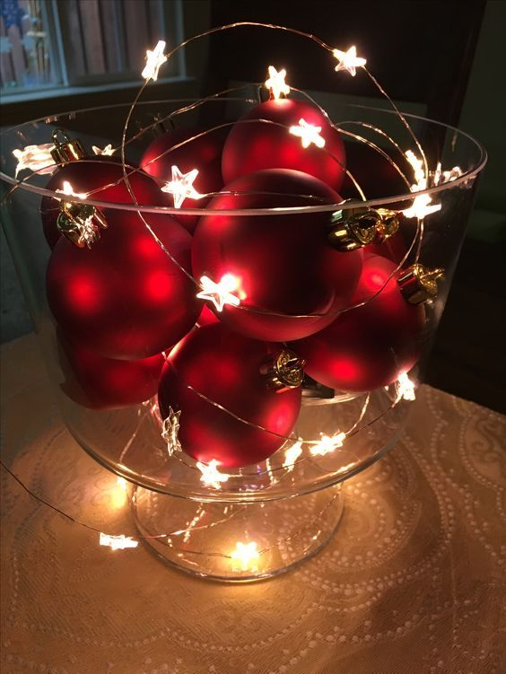 a glass bowl with red Christmas ornaments and a star light garland is a cool winter decoration