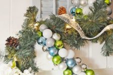 a green, white and blue Christmas ornament garland over the fireplace for cool holiday decor