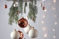 a holiday chandelier of a white wreath, evergreens and small copper and white ornaments for Christmas