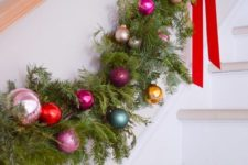 a lush evergreen and colorful Christmas ornament garland with red bows is a cool railing decor idea