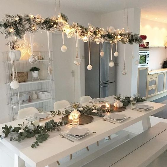 a snowy Christmas branch with lights and white ornaments hanging down overhead is a modern feel