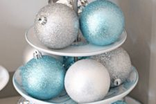 a stand with silver and blue glitter Christmas ornaments is a nice centerpiece or some other decoration