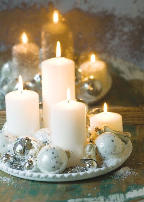 a white tray with white and silver Christmas ornaments and pillar candles plus faux snow is a gorgeous centerpiece