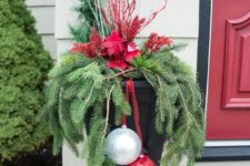 an outdoor urn with evergreens, white branches, red blooms and a giant silver and red ornament