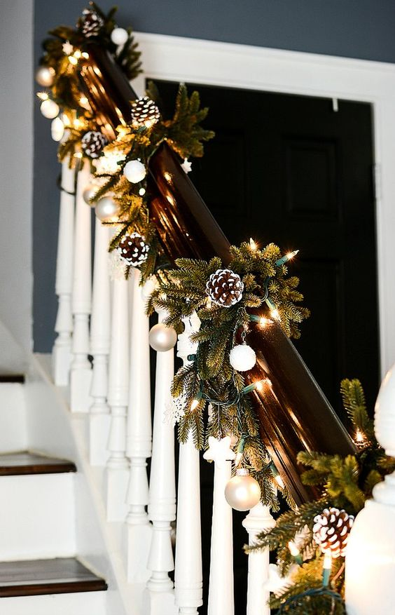 chic railing Christmas decor with lights, evergreens, metallic nd white ornaments is a stylish farmhouse idea
