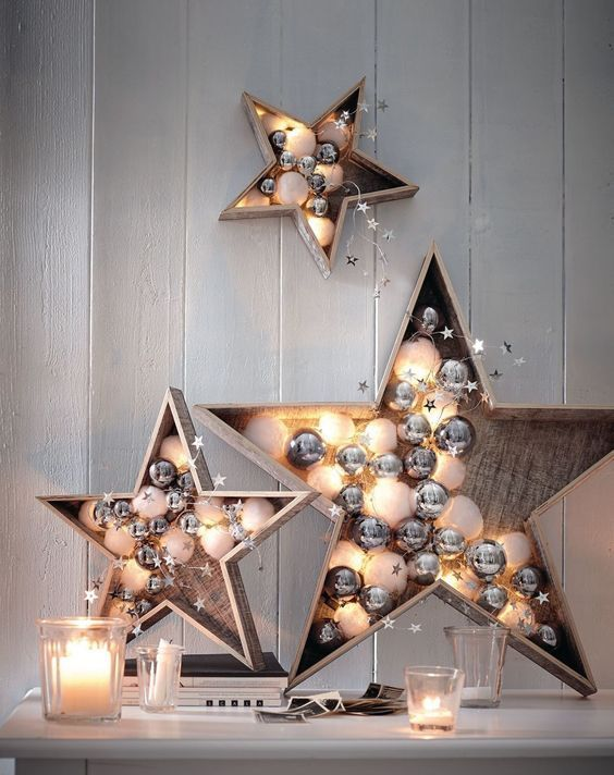 plywood stars filled with white and silver ornaments and lights are cute and chic festive decor options