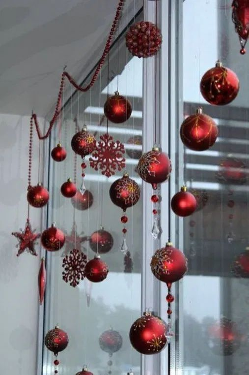 red Christmas ball and snowflake ornaments and beaded garlands to decorate a window