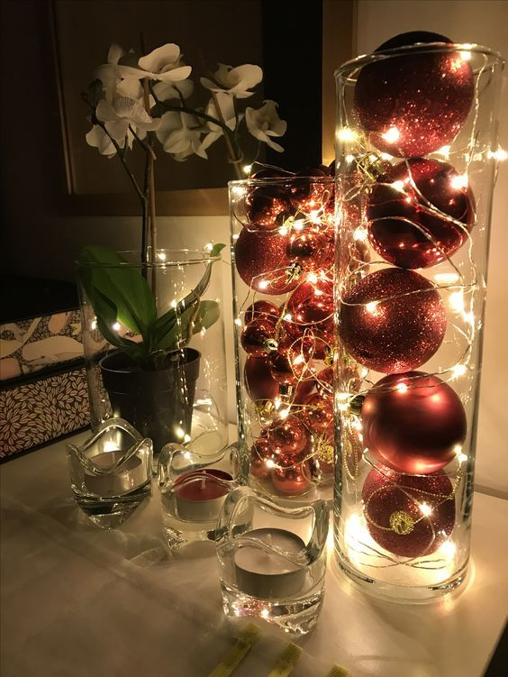 tall glass vases filled with red and red glitter ornaments and lights are amazing as holiday decor