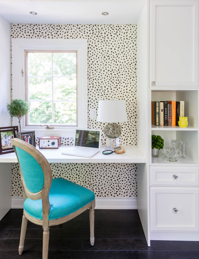 Dark hardwood flooring and a wallpaper with animal pattern is an interesting mix for a compact feminine home office design. (Carriage Lane Design-Build Inc.)