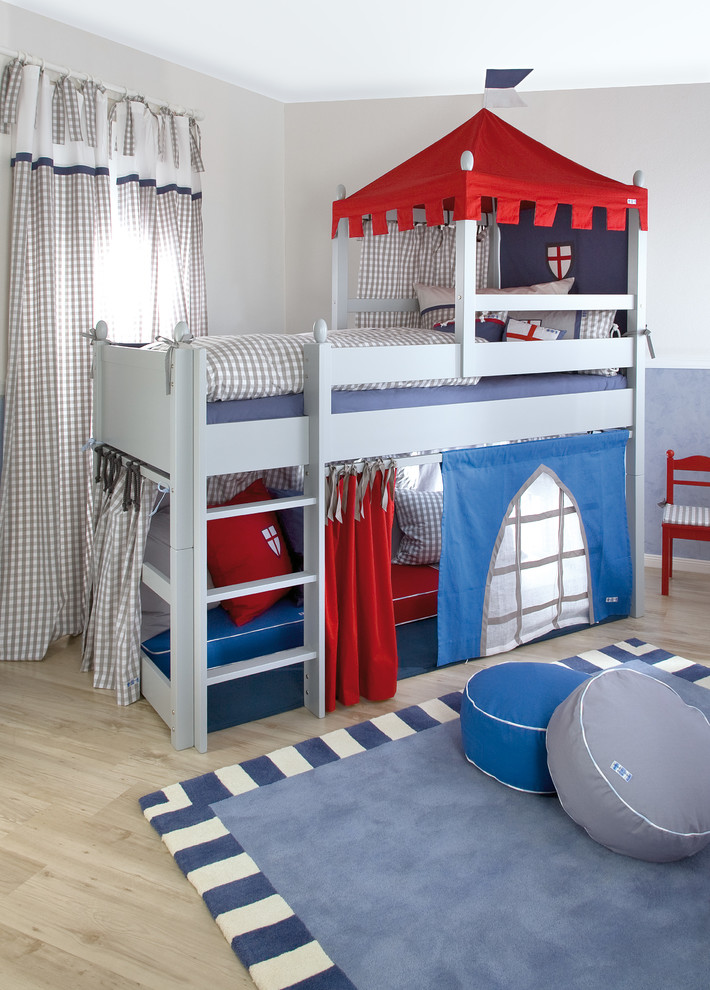 This boys bedroom in nice grey, blue and red tones doubles as a fun playroom.