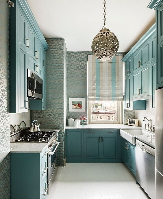 a beautiful turquoise kitchen with white countertops, a window instead of a backsplash and vintage faucets