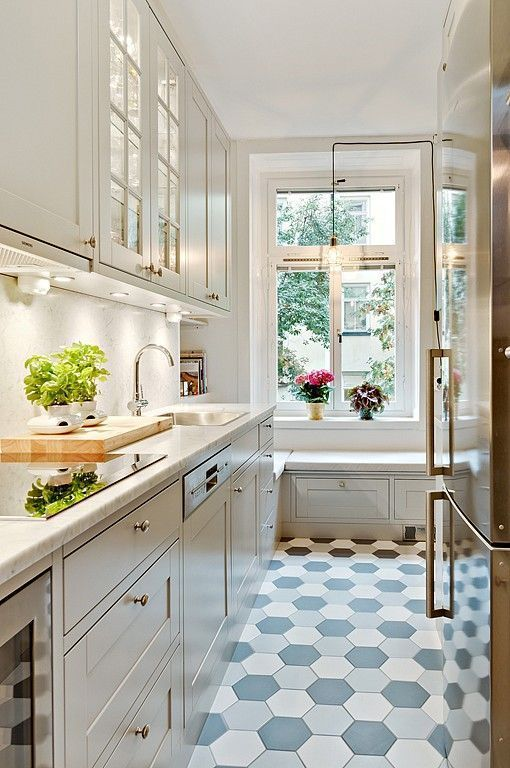 a beautiful white kitchen with white countertops, a white backsplash, a hex tile floor and a windowsill bench