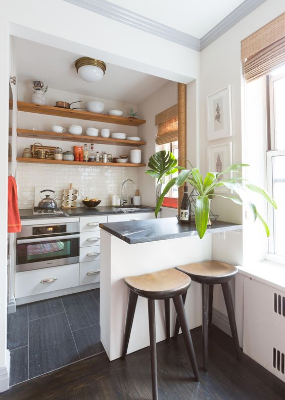 a chic modern kitchen with white cabinets, black countertops, open shelves, potted greenery and wooden stools